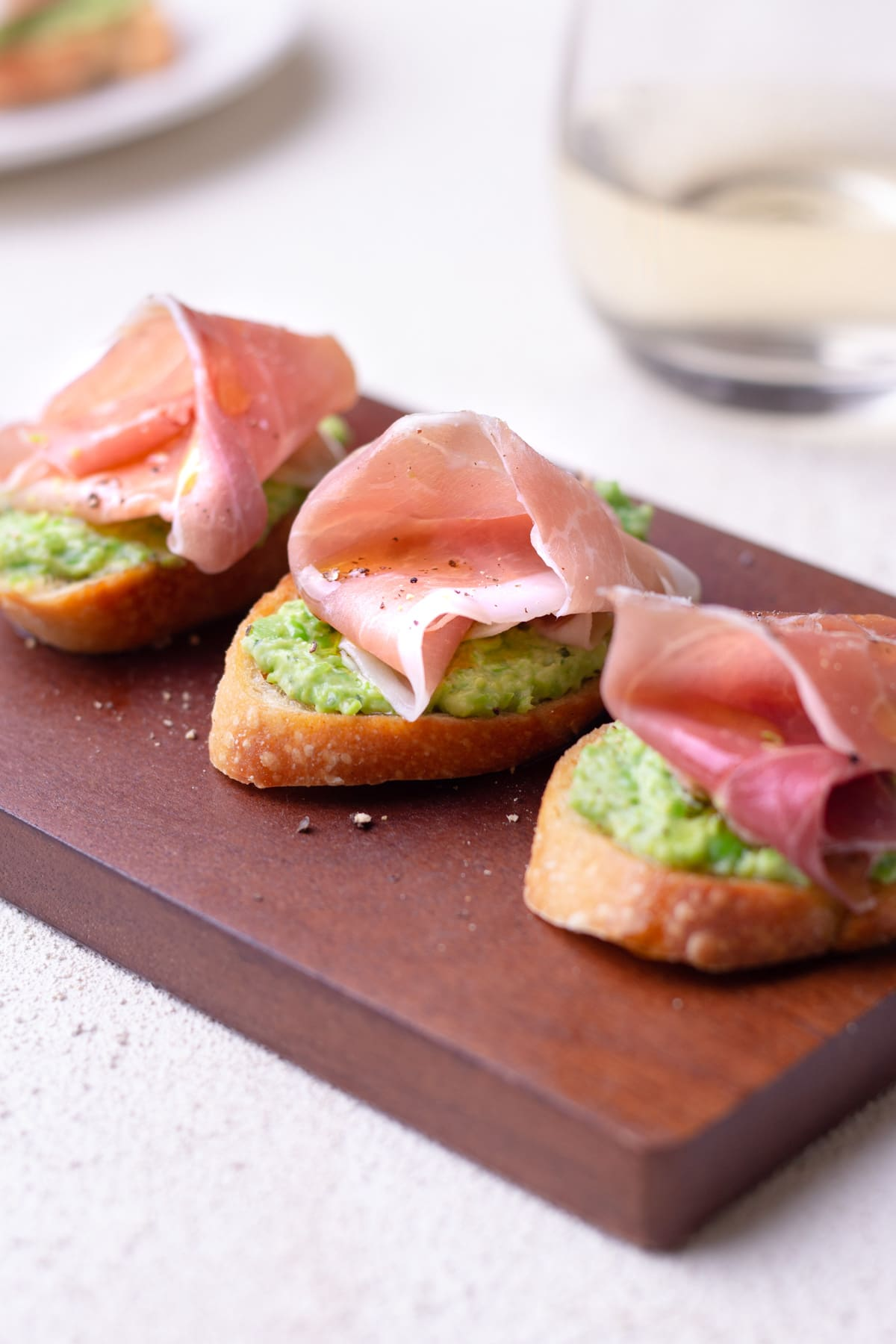 Closeup straight on shoot of 3 crostini top with pea and ricotta puree and prosciutto on a cutting board.