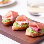 Crostini topped with pea-ricotta spread and prosciutto on a cutting board with white wine and a plate in the background.