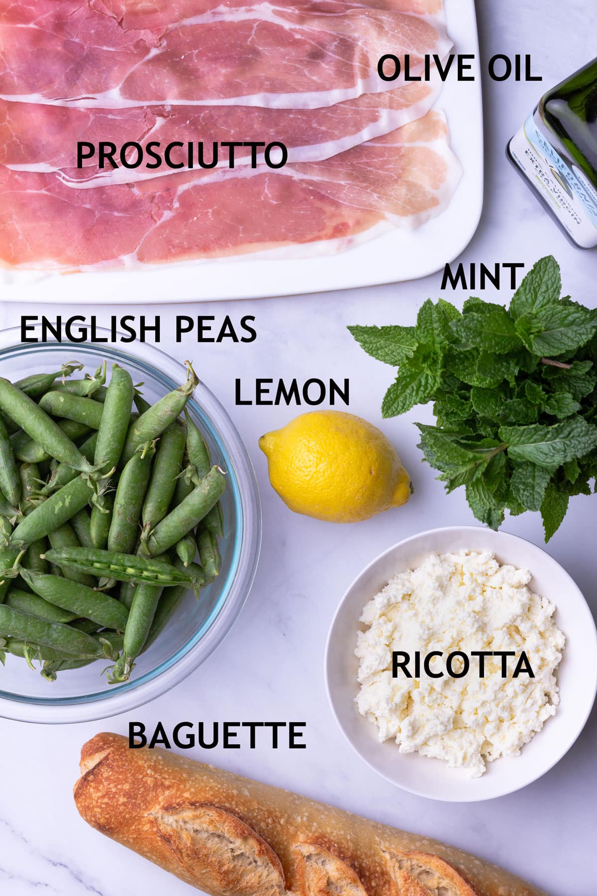 Overhead view of ingredients for crostini including prosciutto, olive oil, fresh English peas, lemon, mint, ricotta cheese and a baguette.