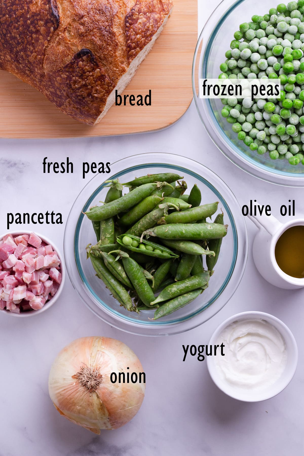 Overhead view of ingredients for soup including fresh and frozen green peas, pancetta, bread, olive oil, onion and yogurt.