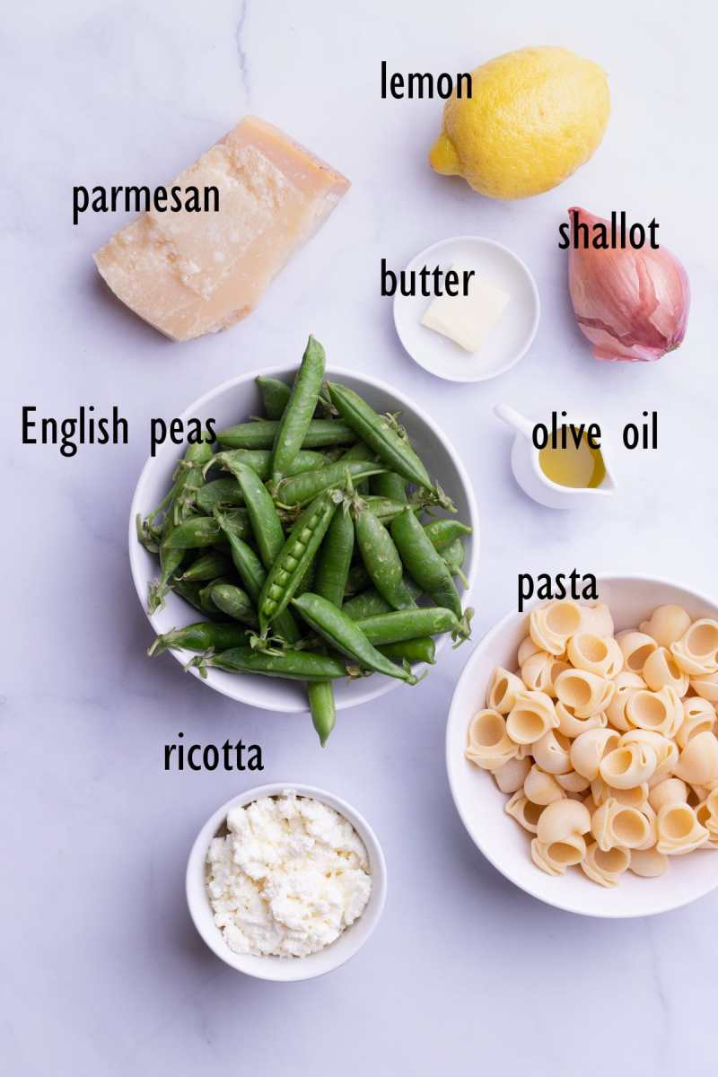 Overhead view of ingredients including English peas in the pod, butter, olive oil, a shallot, a lemon, ricotta and pasta.