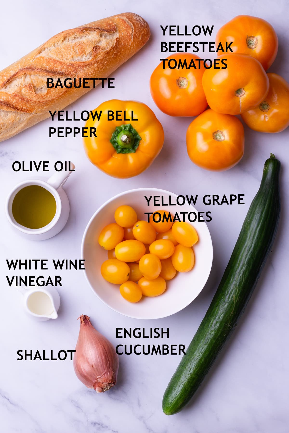 Overhead view of ingredients for gazpacho including bread, yellow tomatoes, a yellow bell pepper, an English cucumber, a shallot, olive oil, and white wine vinegar.