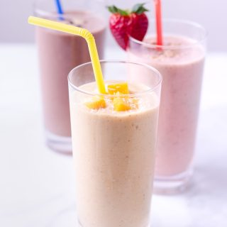 Three oat smoothies, including strawberry banana, turmeric mango and chocolate peanut butter straight on in glasses with straws on a marble surface.