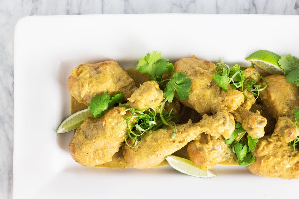 Overhead, closeup view of a platter of Curry Chicken Legs.