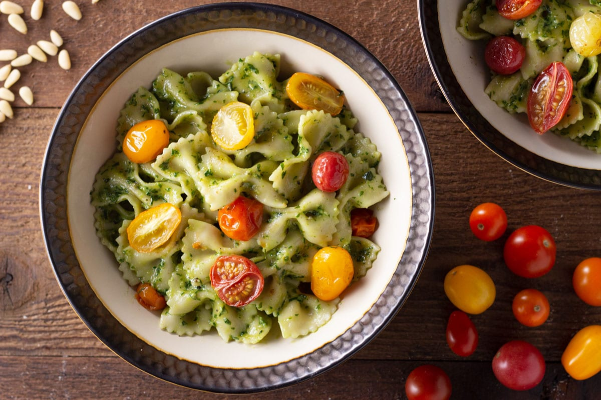 Overhead view of two bowls of pesto pasta with roasted multi-colored grape tomatoes on a wood surface.