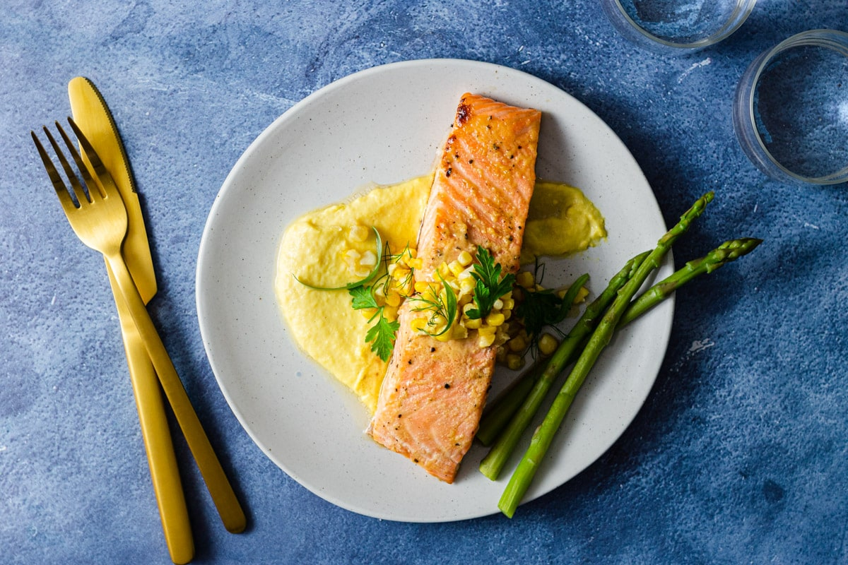 Overhead view of a plate of salmon over a corn puree next to asparagus surrounded by a fork and knife and water glasses.