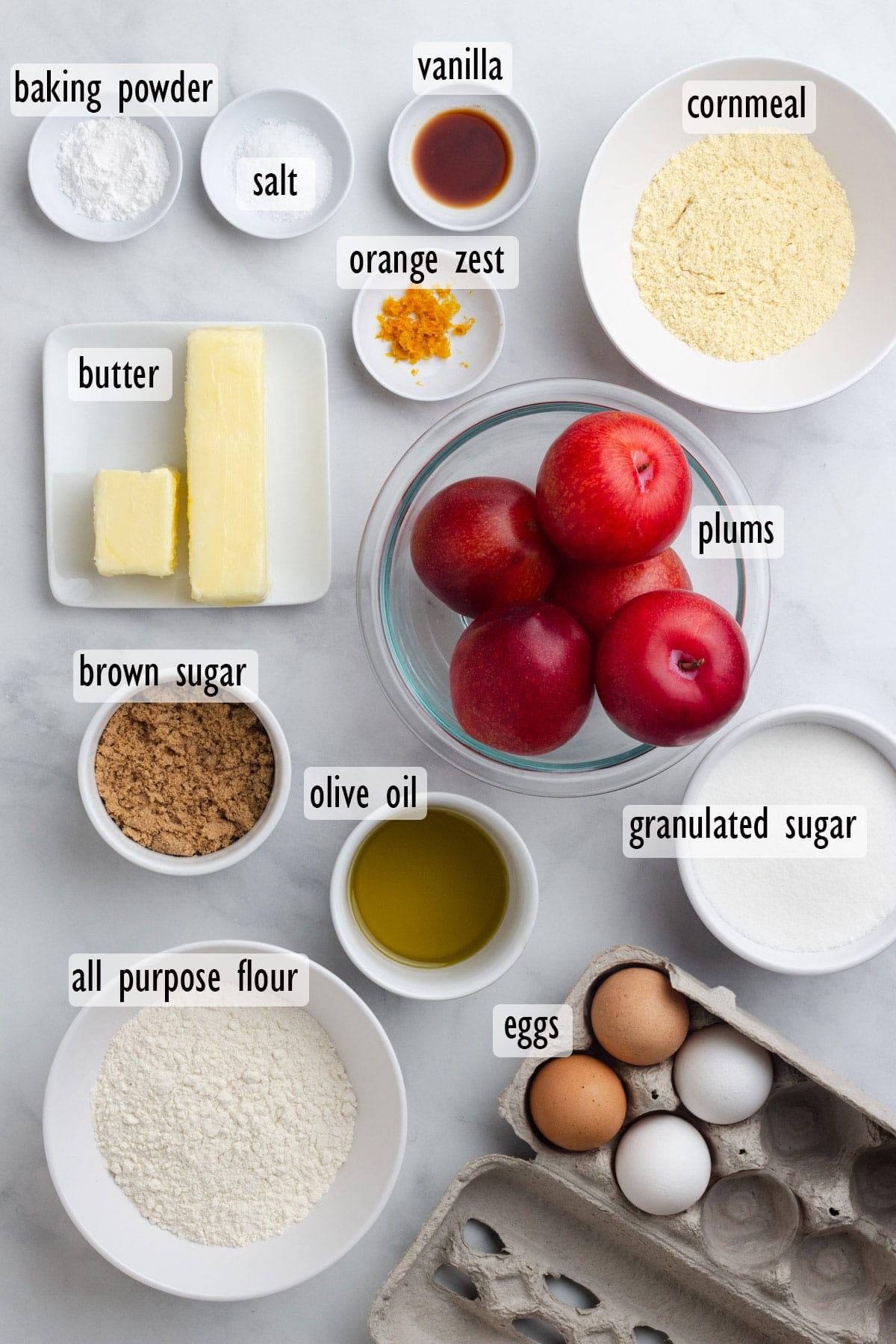Cake Ingredients, including red plums, eggs, cornmeal, flour, white sugar, brown sugar, butter, olive oil, baking powder, salt, vanilla and orange zest.