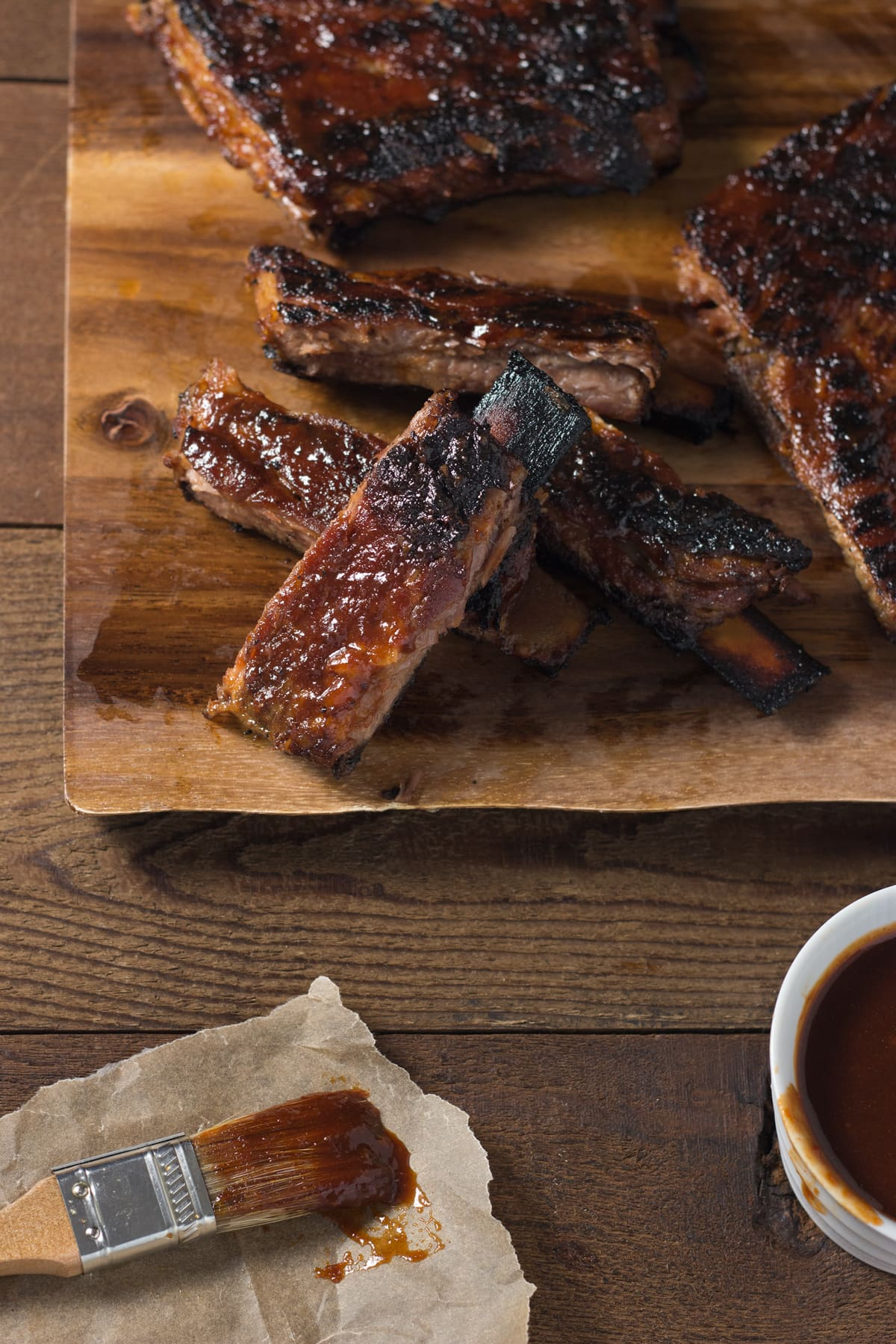 Group of Korean BBQ pork ribs on a cutting board next to a bowl of barbecue sauce and a pastry brush.