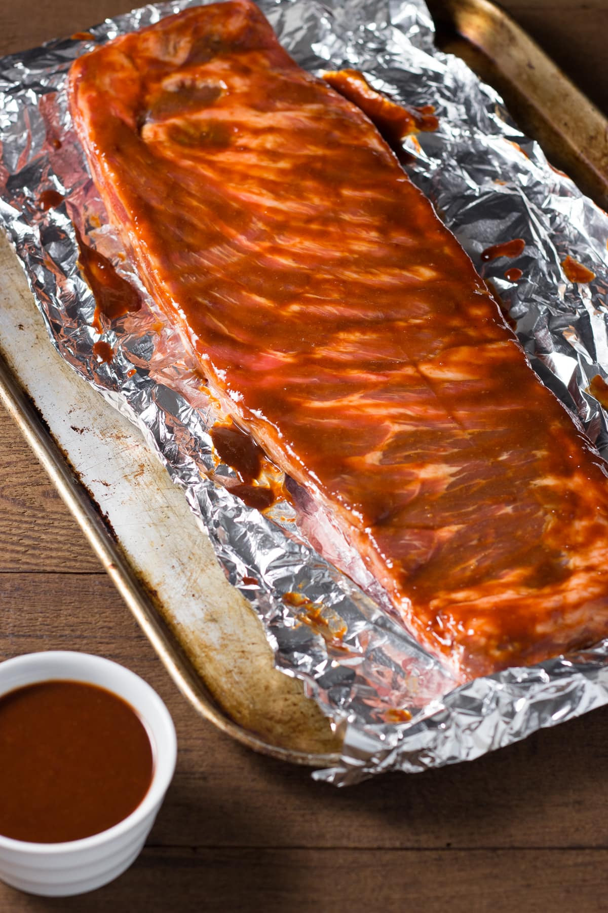 Rack of raw pork spare ribs on foil on a sheet tray brushed with barbecue sauce.
