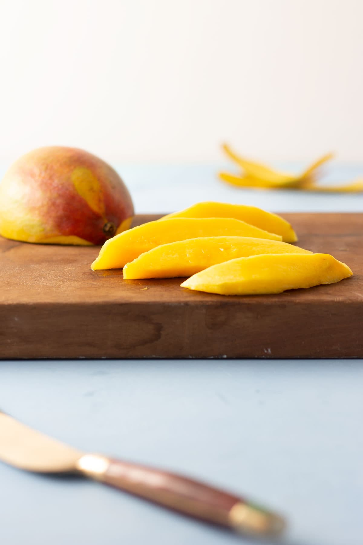 Fresh mango slices and half a mango on a cutting board with a knife in the forefront.