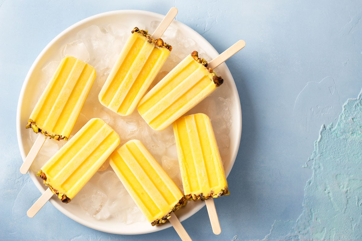 Overhead view of a group of Mango Lassi Popsicles with Pistachios.