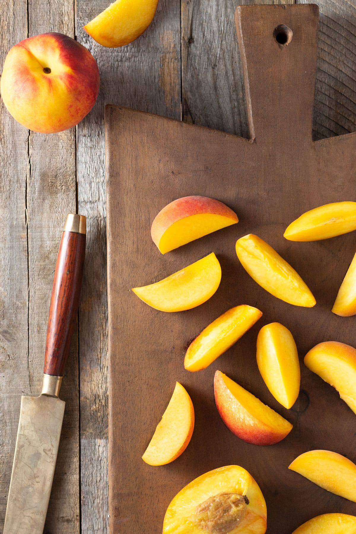 Sliced Peaches on a wood cutting board next to a whole peach and a knife.