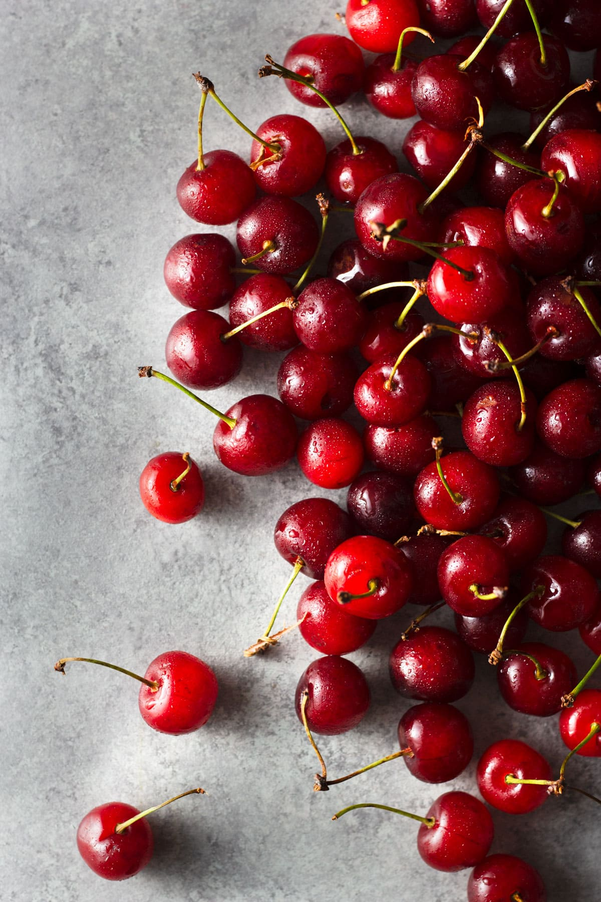 Overhead view of a group of sour cherries on a light grey surface.