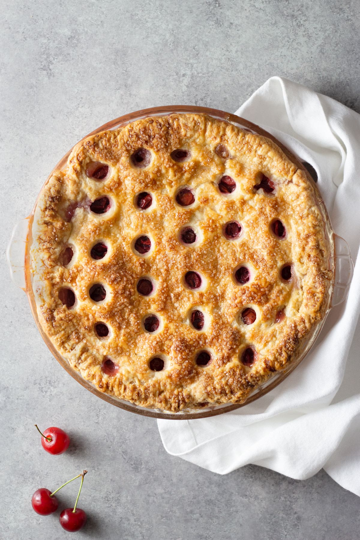Overhead view of a Sour Cherry Pie with circles cut out of the top crust on a grey surface next to cherries and a dish towel.