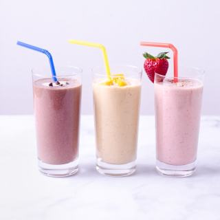 Three smoothies lined up: chocolate, mango and strawberry.