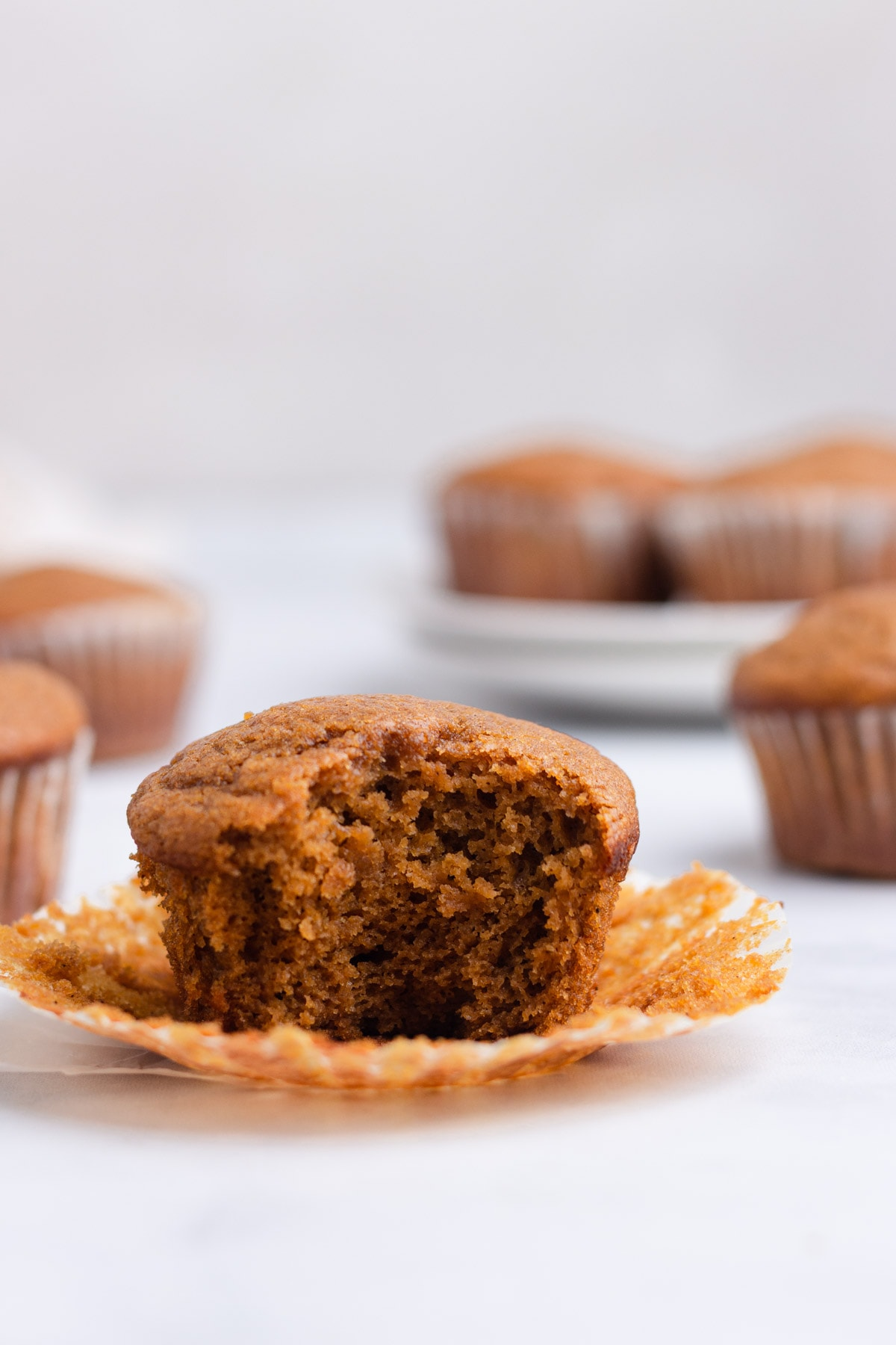 A pumpkin protein muffin with the paper pulled down and a bite taken out of it with more muffins in the background.