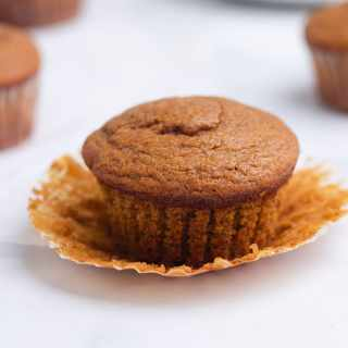 Close up of a Pumpkin Protein Muffin with the muffin paper pulled down with more muffins in the background.