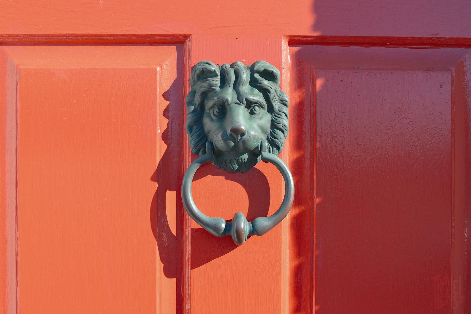 A bronze door knocker on a bright red-orange door