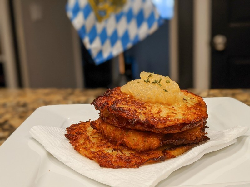 plate of potato pancakes with apple sauce in front of a bavarian flag