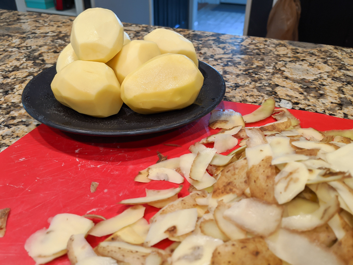 peeled potatoes on a cutting board