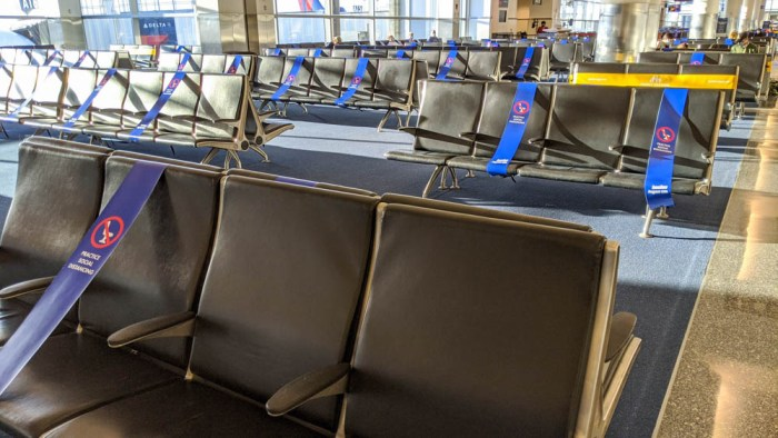 social distancing signs across seats in an empty airport terminal because of the pandemic