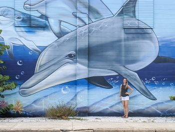 Large dolphin mural and me standing in front of it