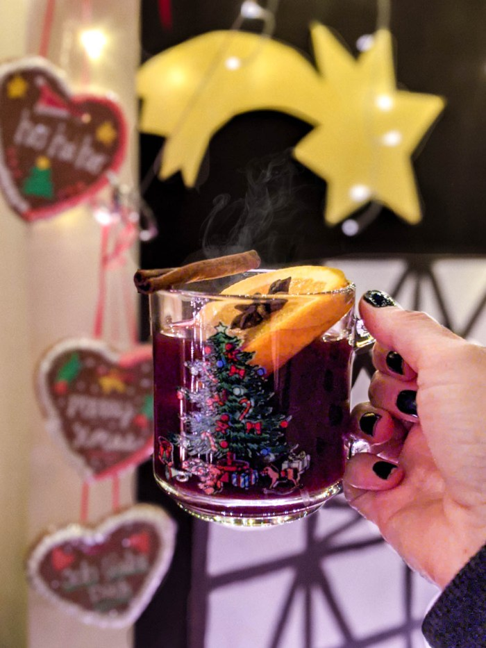 glass of gluhwein in a cute christmas mug in front of lebkuchenherzen and christmas star