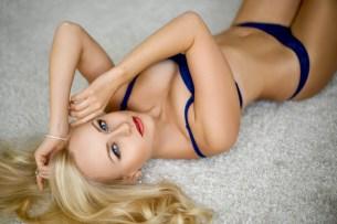 Sexy Blondine lauert auf dem Teppich