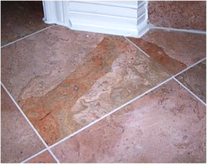 This water-damaged linoleum shows signs of buckling and discoloration.