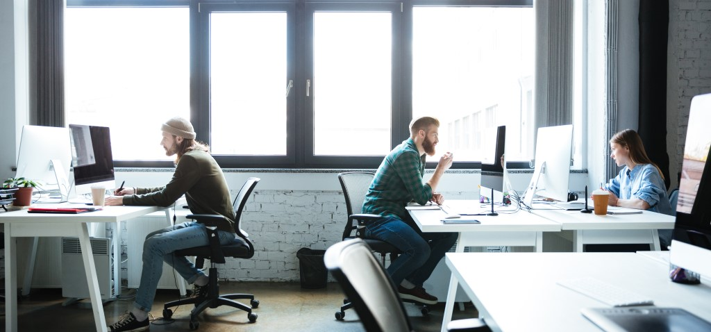 Tres personas trabajan en ordenadores de pantalla grande en una oficina bien iluminada y espaciosa.