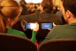 A female and a male is sitting next to each other in theater seats. Both are holding up their mobile phone, looking at captions that is in sync with the movie.