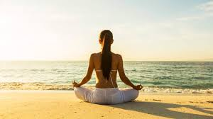 woman meditating in beach