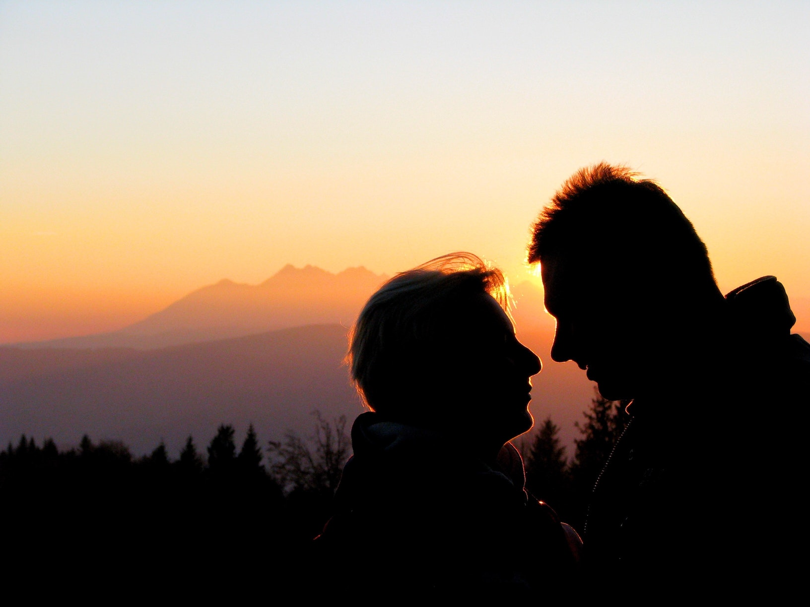 Man and his woman looking at each other with sun in the background creating a silhouette effect - courtship