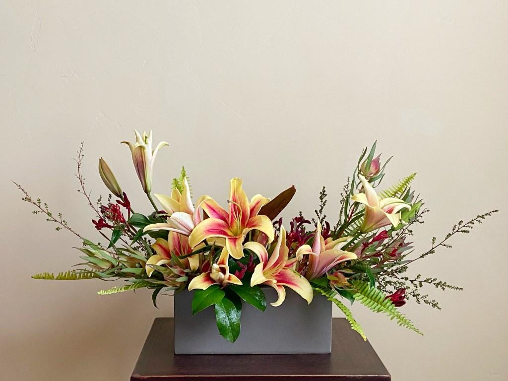 Crescent shaped yellow oriental lily arrangement