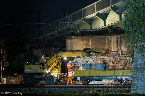Schienenbagger und Anhänger mit Bauelementen unter Brücke. Bild: © RMV / Jana Kay