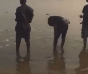 Suspected Yahoo Boys Seen Throwing Money Into A Dirty River As They Make Prayers (Video)
