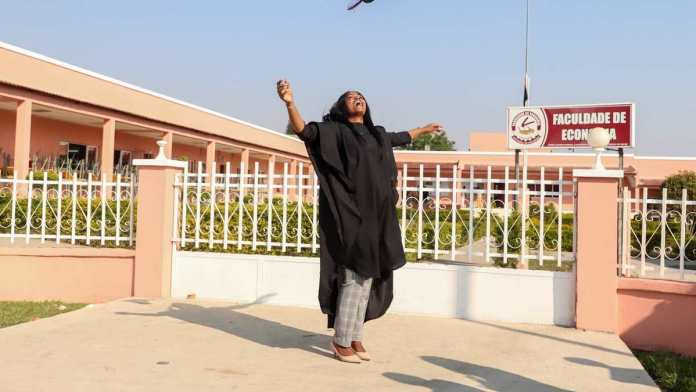 student in a convocation gown tossing her hat