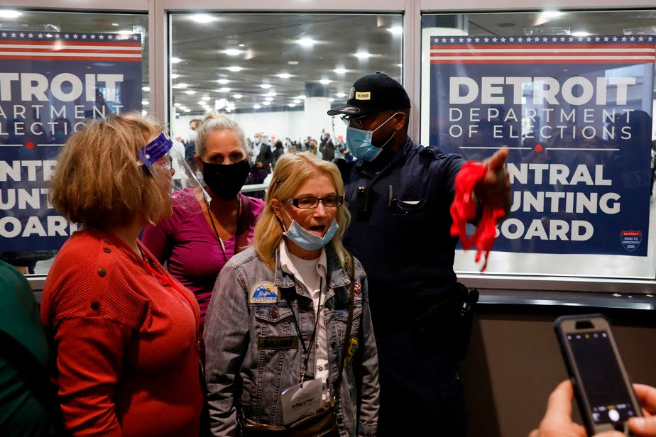 A policeman shows the exit door to a woman who showed up with dozens of other Donald Trump supporters at the TCF Center in Detroit, Mich., In an attempt to stop the counting.