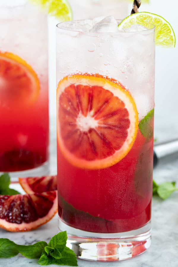 a blood orange mojito that looks like a sunset with the blood orange juice on the bottom and the clear bubbly club soda on top