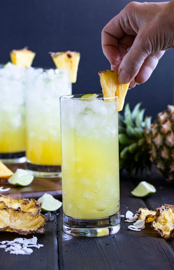 a hand placing a pineapple wedge to garnish the cocktail