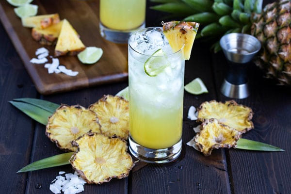 a pineapple and coconut rum drink with dried pineapple slices all around