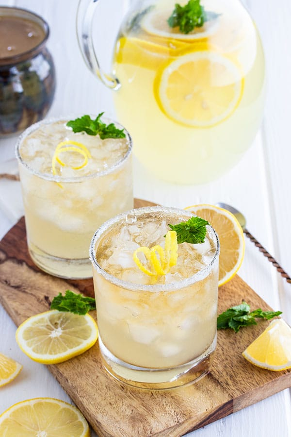 two glasses and a pitcher of whiskey lemonade