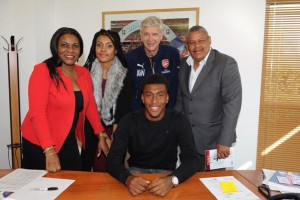 Alex surrounded by parents, sister and Arsene Wenger as he pens a new contract