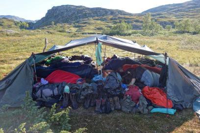 Tarp mit Gepäck und Menschen in Schlafsäcken
