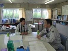 現場事務所で中塚主任から説明を受ける中山社長