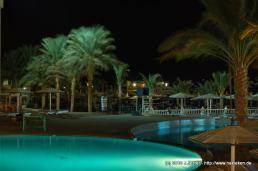 Beleuchteter Pool mit Strand bei Nacht