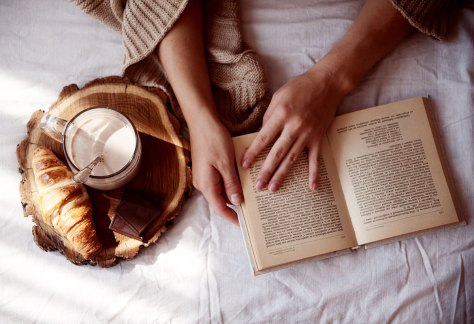 woman with cocoa, croissant, and a book