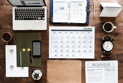 desktop with laptop, calendar, notes, coffee etc