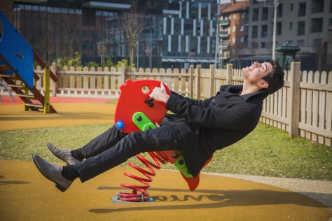 man on playground rocking horse