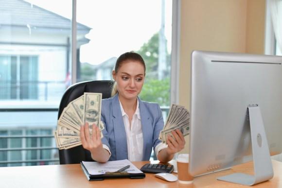 woman holding large amount of money